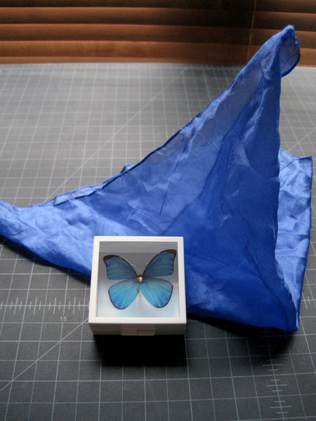 You can combine Magic Butterfly with T-212 Ballerina Hank. You start off with the blue butterfly in the box and then drape a blue silk over it. The silk is removed and it appears that the butterfly has disappeared. Suddenly, the blue silk becomes animated and gracefully dances in the air.  The blue and yellow silks from Crystal Tube are the perfect color and size for this.
