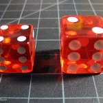 Close-up of props. Standard sized die from Crash Dice and larger die from The Great Escape